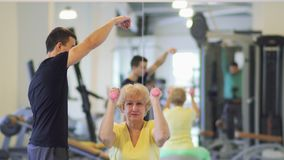 Elderly woman makes exercise with dumbbells in the gym with trainer. Elderly woman makes sport exercises with dumbbells in the gym with trainer. She sits on stock footage
