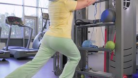 Old woman squats in the gym