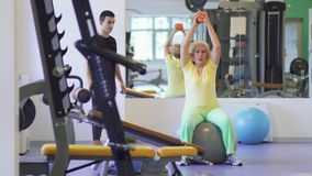 Elderly woman makes fitness exercise with ball in the gym. Elderly woman makes sport exercises with small ball in the gym with trainer. She sits on fitness ball stock video