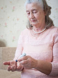Elderly woman makes testing high blood sugar. Stock Photo