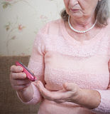 Elderly woman makes testing high blood sugar. Royalty Free Stock Photography