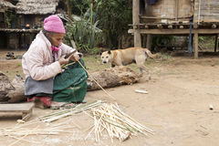 Elderly Woman Making Baskets. An elderly, northern Laos hill tribe woman gently skins the top layer off strips of bamboo in preparation for basket weaving in her Royalty Free Stock Images
