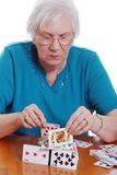 Elderly woman making a house with playing cards. Isolated elderly woman making a house with playing cards on a white background royalty free stock images