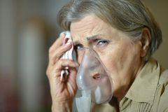 Elderly woman making inhalation Stock Photos