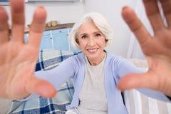 Elderly woman making self photos stock images