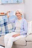 Elderly woman making self photos stock image