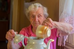 Elderly happy woman making tea in the kettle. Royalty Free Stock Photography
