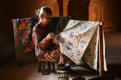 Elderly woman making traditional batik Stock Photo