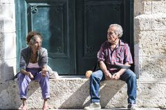 Elderly couple resting on plinth in Havana, Cuba. Elderly woman and man resting in sunshine on plinth Stock Photos