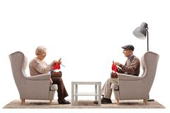 Elderly woman and an elderly man seated in armchairs knitting stock photo