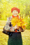 Elderly woman with maple leaves Royalty Free Stock Photography