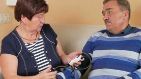 Elderly woman measures the blood pressure at home on the couch. Poor man's well-being. Taking care of his wife about her