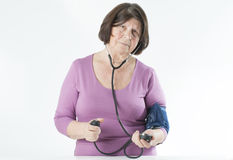 Elderly woman measuring arterial pressure. Stock Images