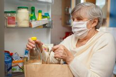 An elderly woman in a medical mask takes food from packages and puts it in the refrigerator