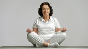 Elderly woman meditating on an exercise mat stock video
