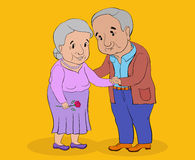 An elderly woman and a middle-aged man standing and holding hand. Gray-haired elderly woman and a middle-aged man standing and holding hands, smiling Royalty Free Stock Images