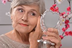 Elderly woman with mirror Stock Images