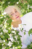 An elderly woman near the blooming tree. Beautiful older woman with blond hair next to a blooming tree in the garden in may Stock Image