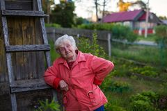 An elderly woman near her house in the village. Summer. Royalty Free Stock Photo