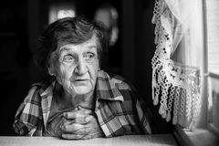An elderly woman near the window. Loneliness. Stock Image