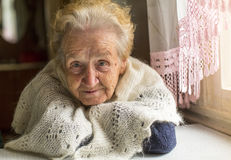 Elderly woman near the window. Stock Image