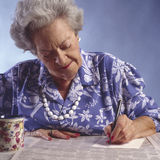 Elderly woman with newspaper classified section#1 Royalty Free Stock Photo