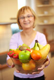 Elderly woman offering fruits Royalty Free Stock Photos