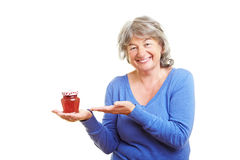 Elderly woman offering homemade jam Stock Photo
