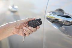 Elderly woman open car door on key alarm systems Royalty Free Stock Photos
