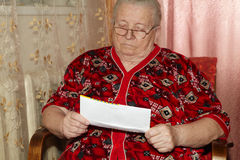 Elderly woman and open letter Stock Images