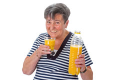 Elderly woman with orange juice Stock Photography