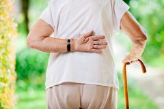 Elderly woman outdoors with back pain. Elderly woman outdoors with lower back pain royalty free stock photos