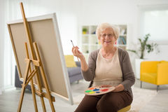 Elderly woman painting on a canvas. Seated on a chair at home royalty free stock photography