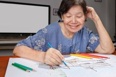 Elderly woman painting color on her drawing at home. Elderly woman painting color on her drawing  , hobby at home Royalty Free Stock Photography