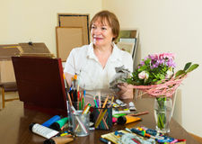 Elderly woman painting for fun at home Stock Photography