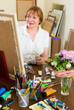 Elderly woman painting for fun at home Stock Images