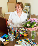 Elderly woman painting for fun at home Stock Photos