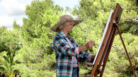 Elderly woman painting in the park stock video footage