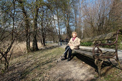 Elderly Woman In Park. An elderly grandmother is enjoying the sun in a park in spring Stock Photos