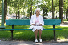 Elderly woman in park. 83 years old elderly woman sitting on a bench in a park in sorel-tracy, quebec, canada stock photography
