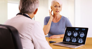 Elderly woman patient telling her doctor about an ache in her neck Stock Photography