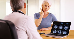 Elderly woman patient telling her doctor about the pain in her neck Stock Image