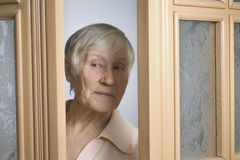 Elderly Woman Peeking Through Doorway Stock Image