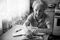 Elderly woman pensioner with bills to pay utilities. Problems. Stock Photos