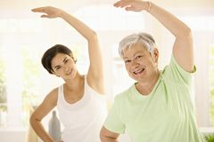 Elderly woman with personal fitness trainer. Healthy elderly woman doing exercises with personal trainer at home, smiling stock images