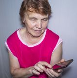 An elderly woman with a phone in her hands royalty free stock images