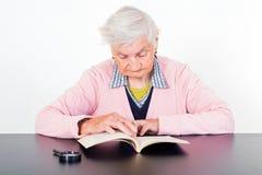 Elderly woman. Photo of elderly woman reading a book Royalty Free Stock Photos