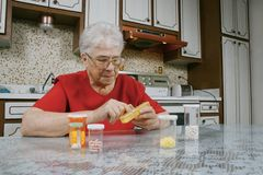 Elderly woman and pills Royalty Free Stock Image