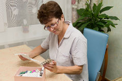 Elderly woman with pills and instructions Stock Photography