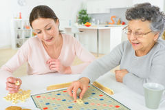 Elderly woman playing board game Stock Image